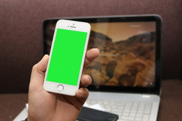 Smartphone with green screen and a laptop